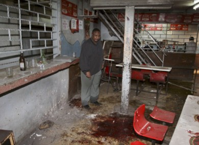 Pub-owner Charles Mwaura observes the bloodstained floor at the scene of a suspected grenade blast at his pub in downtown Nairobi, Kenya early today