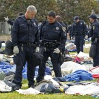 Oakland police officers sift through possessions left behind by Occupy Oakland protesters after yesterday's eviction. (AP Photo/Ben Margot)