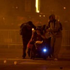 Protesters huddle together after police use tear gas to disperse the crowd last night. (AP Photo/Darryl Bush)