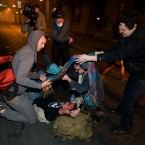 Occupy Wall Street protesters help a man injured after police used tear gas to disperse a large crowd of protesters. (AP Photo/Darryl Bush)