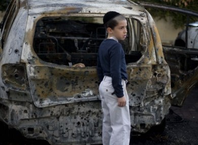 A boy stands next to a burned cars following Saturday night's rocket attacks from the Gaza Strip, in Ashdod, southern Israel, early Sunday, 30 October.