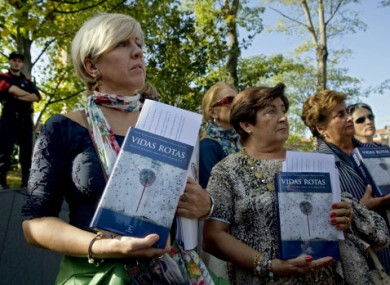 Relatives of people killed by the Basque armed group ETA protest with several books with the history of more than eight hundred people killed by ETA, during the International Conference in San Sebastian, northern Spain on Monday.