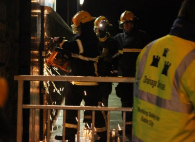 Firefighters work to break the padlocks on the open floodgates in Sandymount last night