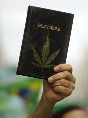 A man holds a bible covered by an image of a cannabis leaf during a march in favor of the legalization of marijuana in Sao Paulo, Brazil (File)