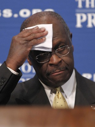Herman Cain wipes his forehead before answering questions at the National Press Club in Washington yesterday.