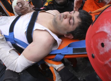 A survivor is pulled from the rubble of the hotel