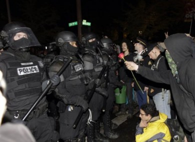 Occupy Portland protesters offer riot police a rose.