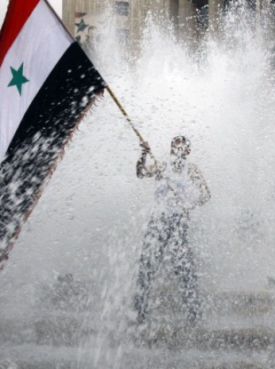 A pro-Syrian regime protester, waves a Syrian flag from a fountain during a demonstration in Damascus, Syria