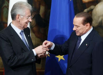 Silvio Berlusconi presents Mario Monti with a small ceremonial bell - used by prime ministers to call cabinet meetings to order.