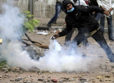 A protester throws a tear gas grenade back at Egyptian riot police in Cairo today.