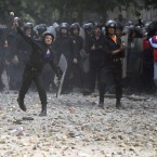 Egyptian riot police throw stones during today's clashes with protesters in Cairo. (AP Photo/Khalil Hamra/PA Images)