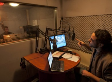 Broadcaster Eyal Raz, right, and technician Nasser Abu Hadwan, left, work in the studio of the