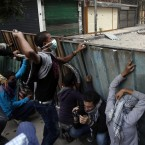 Protesters throw stones as they take cover during today's unrest. (AP Photo/Khalil Hamra/PA Images)