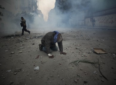 A protester overcome with tear gas inhalation kneels in the middle of the street during clashes with the Egyptian riot police today.