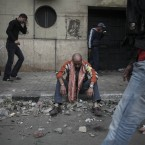 A protester overcome with tear gas inhalation sit on the curb in downtown Cairo. (AP Photo/Tara Todras-Whitehill/PA Images)