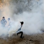 A protester throws a tear gas cannister during today's clashes with Egyptian riot police near Tahrir Square.(AP Photo/Khalil Hamra/PA Images)