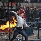 An Egyptian protester throws rocks toward riot police in Cairo earlier today. (AP Photo/PA Images)