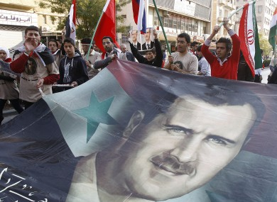 Pro-Syrian regime protesters shout slogans and carry a huge portrait of the Syrian president Bashar Assad during a protest against the Arab League decisions, in Damascus