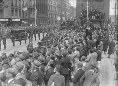 Crowds gather at Nelson's Pillar on O'Connell Street as new President Douglas Hyde's cavalcade passes by on 25 June 1938.
