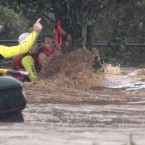 A man is rescued by emergency workers after he was stranded clinging to a tree on a flooded street in Toowoomba, Australia, during a flash flood in January 2011. (AP Photo/ABC/PA Images)