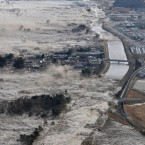 Earthquake-triggered tsunami waves sweep along Iwanuma in northern Japan on 11 March, 2011. (AP Photo/Kyodo News/PA Images)