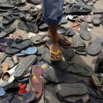 A Bahraini youth stands among the shoes and sandals discarded at the Pearl roundabout in Manama, Bahrain, by people during fierce clashes with police in mid-March. (AP Photo/Hasan Jamali/PA Images)