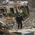 A man searches for a family members in the ruins of tsunami-hit area in Onagawa, Miyagi Prefecture on 20 March, 2011.  (AP Photo/Shuji Kajiyama/PA Images)
