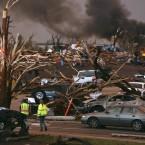 Emergency personnel walk through a neighbourhood severely damaged by a tornado near the Joplin Regional Medical Center in Joplin on 22 May, 2011. (AP Photo/Mark Schiefelbein/PA Images)