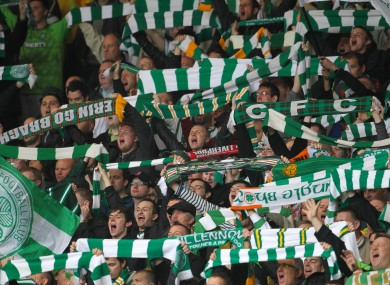 Celtic supporters hold their scarves in the air.