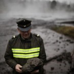 A police officer holds a volcanic rock picked from the overflowed river Nilahue after the eruption of the Puyehue-Cordon Caulle volcano in Los Venados, Chile on 9 June, 2011. (AP Photo/Roberto Candia/PA Images)