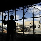A rebel fighter flashes the victory signs as he guides reporters inside a building used by snipers loyal to Libyan leader Muammar Gaddafi during fighting with rebels for the control of Tripoli Street in Misrata, Libya, June 2011. (AP Photo/Hassan Ammar/PA Images)
