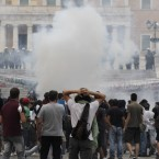 Riot police and protestors at Syntagma Square in Athens were separated by a cloud of tear gas on 29 June as protests against austerity measures hit a climax. Greece has since changed government and teetered on the edge of financial default. (AP Photo/Petros Giannakouris)