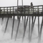 Concerned fisherman Denis Hromin checks on North Carolina's Avalon Fishing Pier after it was battered by wind and rains from Hurricane Irene in August. The storm caused dozens of deaths as it travelled through the Caribbean and along the eastern US coast. (AP Photo/Charles Dharapak/PA Images)
