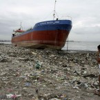 A woman walks past an oil tanker on 28 Sepember which was washed ashore by Typhoon Nesat overnight that also destroyed an undetermined number of shanties and forced the evacuation of thousands of residents. (AP Photo/Bullit Marquez/PA Images)