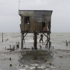 A man hangs on to what remains of a house that was built on stilts as he tries to recover belongings after Typhoon Nesat wiped out most of his neighbours' homes along a coastal village north of Manila on 28 September. (AP Photo/Aaron Favila/PA Images)