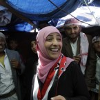 Yemeni activist Tawakkul Karman, one of the three recipients of the 2011 Nobel Peace Prize, reacts as she receives congratulations from protesters at her tent in Change Square in Sanaa, Yemen on 8 October, 2011. Karman's Nobel Peace Prize draws attention to the role of women in the Arab Spring uprisings; they have rebelled not only against dictators but against a traditional, conservative mindset that fears women as agents of change. (AP Photo/Hani Mohammed/PA Images)