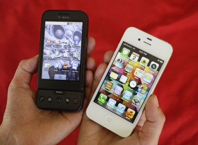 Shown at left is an HTC G1 smartphone offered by T-Mobile and at right is an Apple iPhone 4S smartphone in San Francisco
