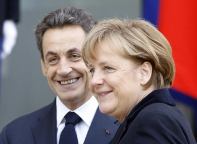 French President Nicolas Sarkozy, left, smiles as he greets German Chancellor Angela Merkel prior to their meeting at the Elysee Palace in Paris, Monday Dec. 5, 2011