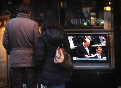 A couple stop to watch a television outside a pub in Dublin as Finance Minister Michael Noonan delivers the budget