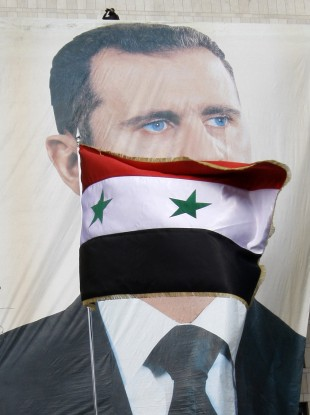 A Syrian flag flies as pro-Syrian regime protesters hold a rally in support of President Bashar Assad, pictured in the large banner, in Damascus, Syria today.