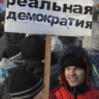 A demonstrator holds a poster reading