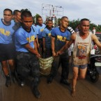Police carry a body after retrieving the victim of a flash flood. (AP Photo/Froilan Gallardo)