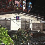Trapped residents perched on a roof in Cagayan De Oro. (AP Photo/Erwin Mascarinas)