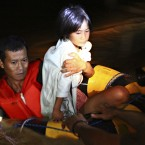 Rescuers carry a girl to safety following a flash flood that inundated Cagayan De Oro. (AP Photo/Erwin Mascarinas)
