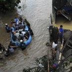 Police use a rubber boat to ferry trapped residents following a flash flood that inundated Cagayan De Oro city. (AP Photo/Froilan Gallardo)