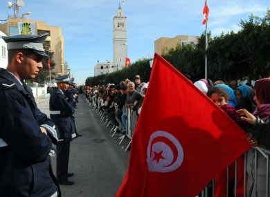 A woman holds a Tunisian flag as she celebrates the first anniversary of the revolution in Sidi Bouzid