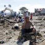 Cristio Tingson talks on his mobile phone as workers search for victims at his buried house on 18 December, 2011 at Iligan city in southern Philippines. Tropical Storm Washi devastated the region with flash floods that killed 1,000 people as they slept and turned two coastal cities into a muddy wasteland filled with overturned cars and uprooted trees. (AP Photo/Bullit Marquez/PA Images)