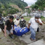Soldiers and health workers carry the body of a flash flood victim in preparation for a mass burial today in Iligan, southern Philippines. (AP Photo/Bullit Marquez/PA Images)