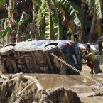 Residents retrieve a car which was washed away in Friday's flash flooding. (AP Photo/Bullit Marquez/PA Images)