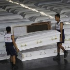 Philippine Navy personnel lift coffins that will be shipped with drinking water, clothes and other relief goods to flood-stricken Cagayan De Oro and Iligan cities, Philippines on 20 December, 2011. Washi was one of the worst disasters to strike in decades. Morgues and funeral homes struggled to cope with the number of dead, running out of coffins and body bags. (AP Photo/Aaron Favila/PA Images)